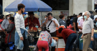 Varias personas sin tapabocas o con su uso indebido caminan por una concurrida calle, en Santa Cruz. (Archivo)   EFE