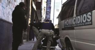 Oficiales de la Felcc levantan el cuerpo de un hombre que falleció en las calles de La Paz. / Foto: APG