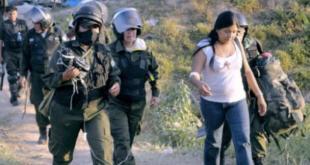 Policías trasladan a una de las marchistas luego de la represión al campamento donde descansaban, en Chaparina.   Foto archivo
